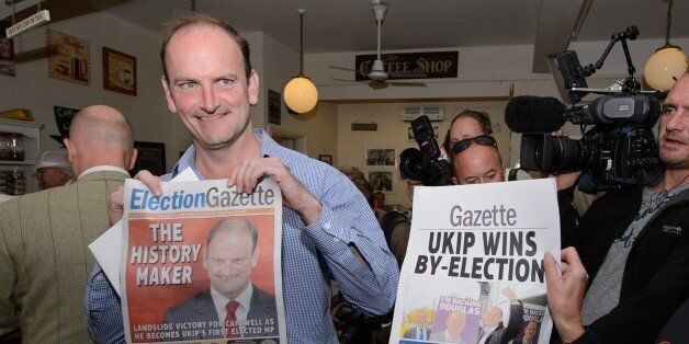 Newly-elected UK Independence Party (UKIP) MP Douglas Carswell (L) poses for photographers with a copy...