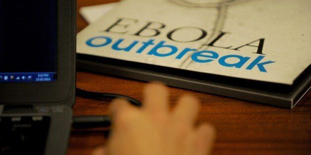 A journalist works near a Ebola hand book distributed by the World Health Organization (WHO) during the...