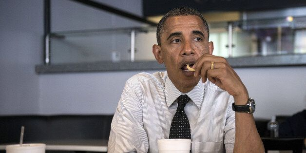 US President Barack Obama eats a french fry while meeting with supporters about voter registration at...