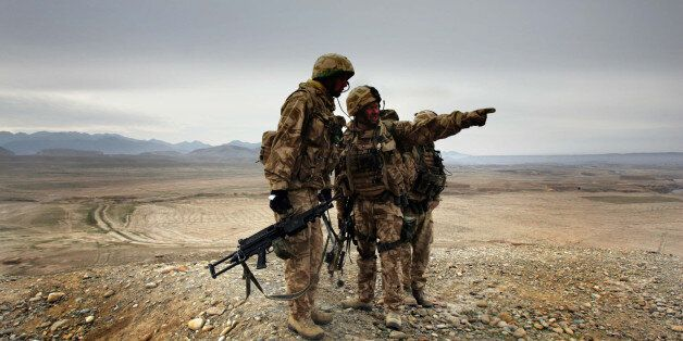 A soldier of 42 Commandos of British Royal Marines points at a location of Taliban militants during an...