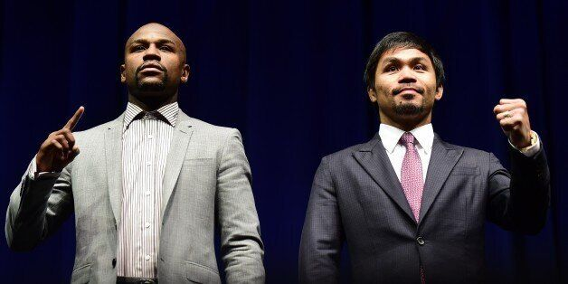 Boxers Manny Pacquiao (R) from the Philippines and Floyd Mayweather from the US gesture while posing...