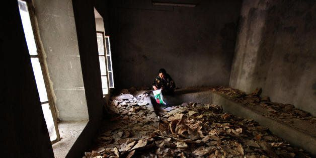 DAHUK, IRAQ: A Yazidi woman sits inside a room covered with bread at the Lalesh temple situated in a...