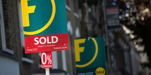 A Foxtons estate agents sign advertises a residential property as 'Sold' in the Brixton district of London,...