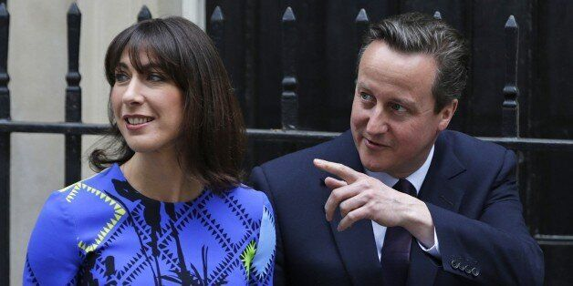 Britain's Prime Minister David Cameron gestures as he walks with his wife Samantha in Downing Street...