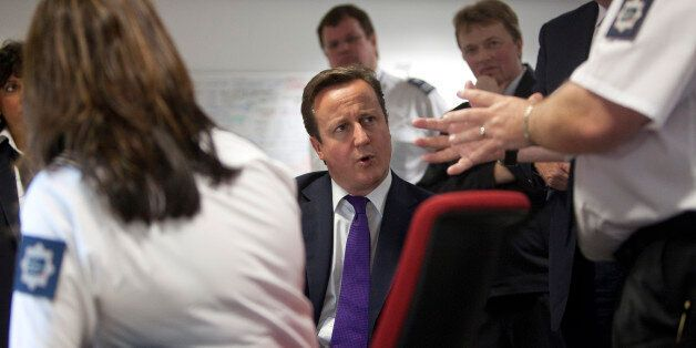 Britain's Prime Minister David Cameron talks with United Kingdom Border Agency officials in their control...