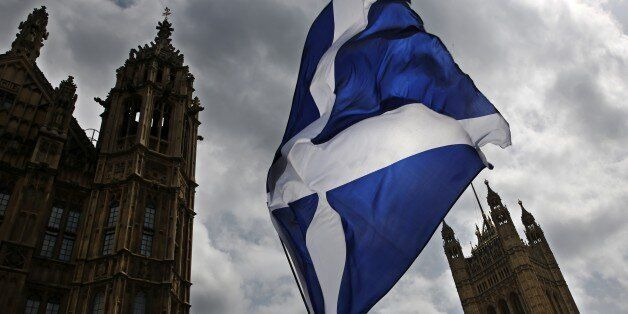 A member of public flies a giant Scottish Saltire flag outside the Houses of Parliament shortly before...