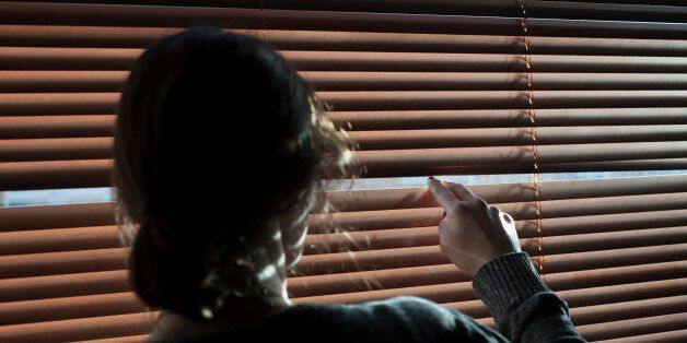 A woman looks out a window through a blind. Picture posed by model - model release
