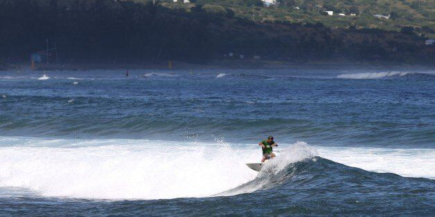 A surfer rides a wave, on April 14, 2015 off Saint-Leu, on the western coast of the French Indian Ocean...