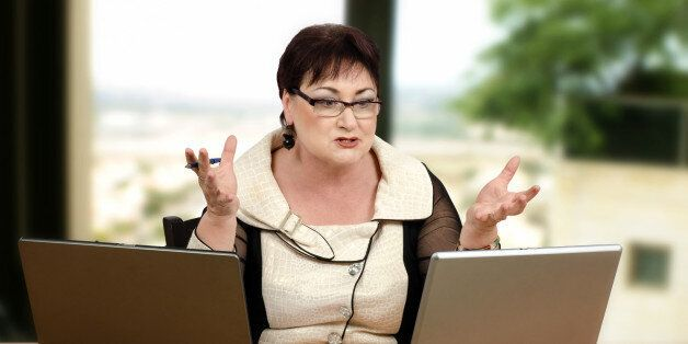 Angry glasses teacher yelling at her student during online lesson. Mature brown haired woman is looking...