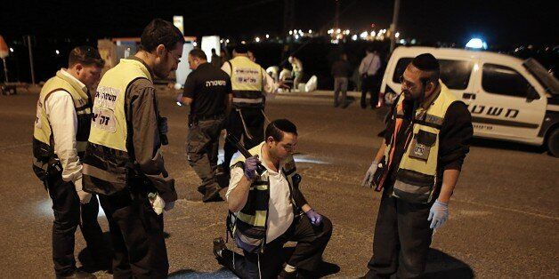 Israeli Zaka emergency services volunteers inspect the site where a Palestinian man stabbed three Israelis...