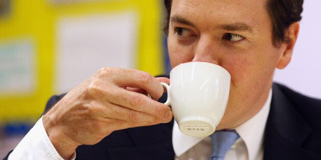 Chancellor of the Exchequer George Osborne enjoys a drink whilst he talks to parents, during a visit...