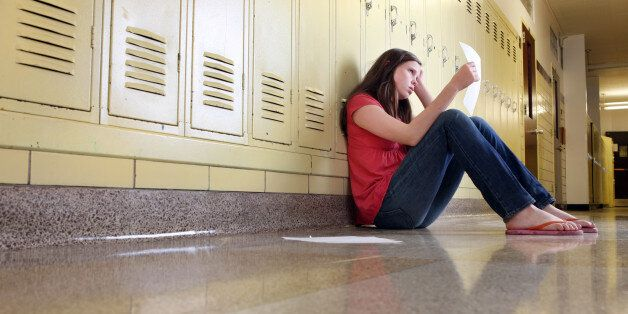 A middle school girl sitting in hallway of school looks upset while looking at her