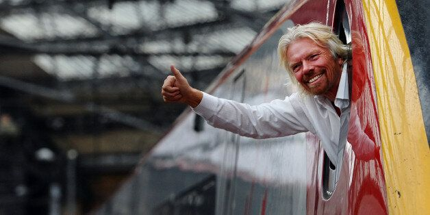 British entrepreneur Sir Richard Branson leans out of the window of the driver's cab on board a Virgin...