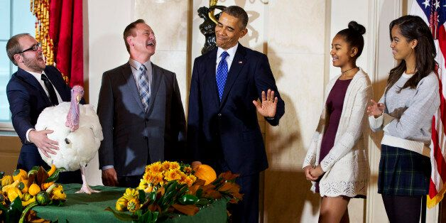 President Barack Obama gestures that his daughters Sasha, second from right, and Malia, right, would...