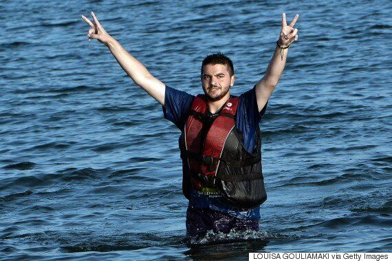 Greek Crisis: Syrian Migrant Pictured Making Victory Signs As He Wades Onto