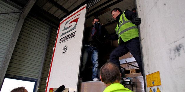 A stowaway passenger climbs down from a lorry trailer helped by UK Border Control after being discovered...