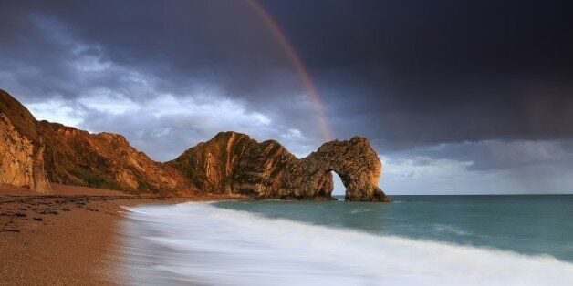 A rainbow over Durdle Door in Dorset. (Photo by: Loop Images/UIG via Getty Images)