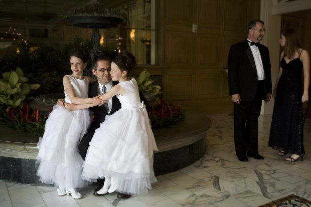 COLORADO SPRINGS, CO  - MAY 16: Robert Moore poses for a photograph with his 9-year-old twin daughters Lauren and Elizabeth on May 16, 2008 in Colorado Springs, Colorado. The annual Father-Daughter Purity Ball, founded in 1998 by Randy and Lisa Wilson, focuses on the idea that a trustworthy and nurturing father will influence his daughter to lead a lifestyle of 'integrity and purity.'   (Photo by Marvi Lacar/Getty Images)