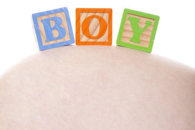 Blocks spelling Boy over mothers tummy.