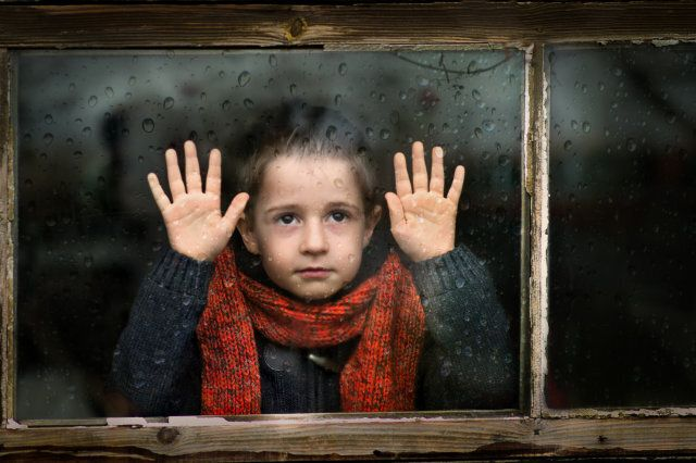 Little boy with red scarf watching through the window