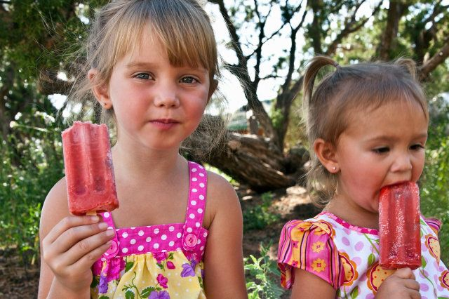 Young girls eating fruit popsicles outdoors