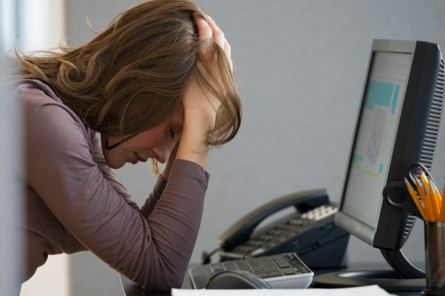 Woman with head buried in hands in office