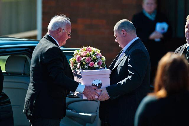 Tuesday 11 March 2014 Pictured: Dad Patrick Mullane (R) helps carry the tiny coffin from the car  Re: A funeral is taking place  in Pontyberem Catholic Church for six day old Eliza-Mae Mullane who died after an incident at the family home in Carmarthenshire in the morning of 18 February 2014, where police later seized two dogs, an Alaskan Malamute called Nisha and a collie cross that were destroyed following the baby girl's death. Parents Sharon John and Patrick Mullane said previously that they would cherish the short time they had with her.