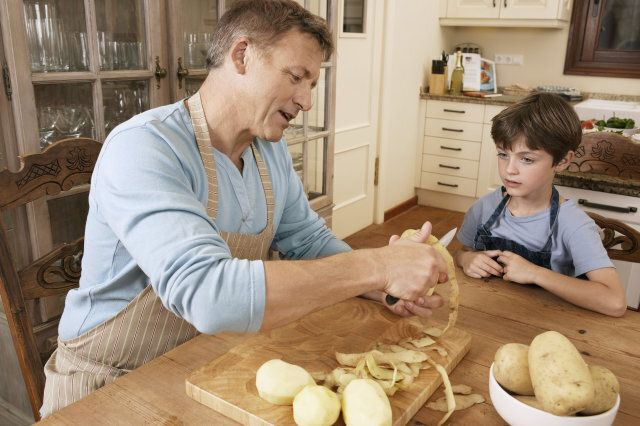 Son watching father peel potato