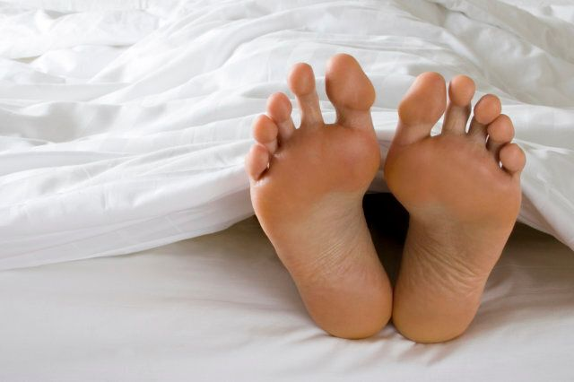 A man's feet poke out of the bottom of a white duvet in bed. Similar images from my portfolio: