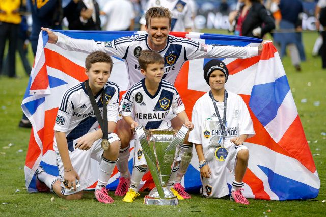 Los Angeles Galaxy's David Beckham, top center, of England, poses with his sons, from left, Brooklyn, Romeo and Cruz after the Galaxy's 3-1 win in the MLS Cup championship soccer match against the Houston Dynamo in Carson, Calif., Saturday, Dec. 1, 2012. (AP Photo/Jae C. Hong)