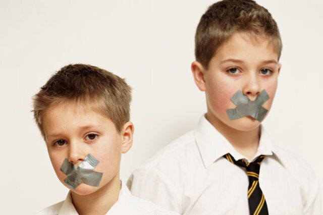 Two boys (10-12) in school uniforms with mouths taped up, portrait
