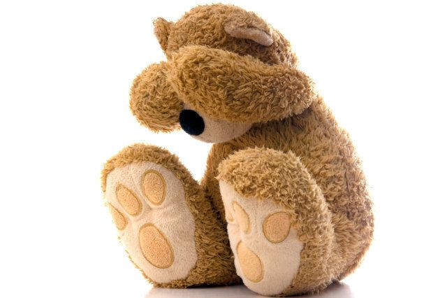 Teddy bear sad and crying into hands.