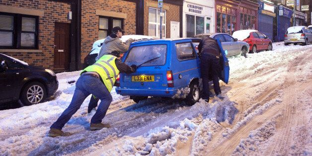 People push a car in snowy conditions in the Crookes area of Sheffield after wild and wintry weather...