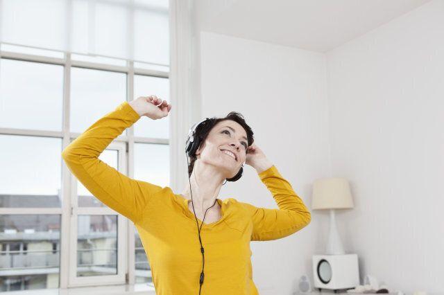 Germany, Bavaria, Munich, Mid adult woman listening music, smiling