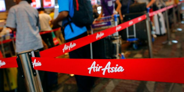 Passengers queue at AirAsia's check-in counters, at the Changi International Airport Monday, Dec. 29,...