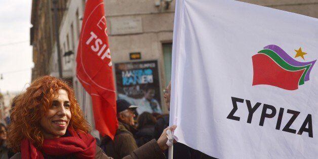 A woman shows a flag of Greek party Syriza on February 14, 2015 in Rome during a demonstration to support...