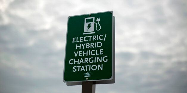 In this Thursday, Feb. 5, 2015 photo, a sign designates a parking space and charging station for electric...