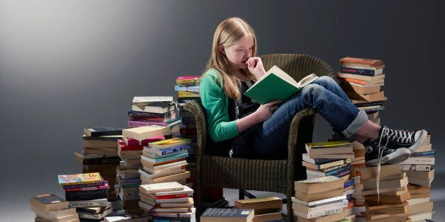 teenage girl sat in chair reading book surrounded by piles of