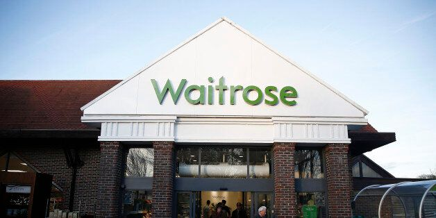 Customers push shopping carts through the entrance of a Waitrose Ltd. supermarket in the Hove district...