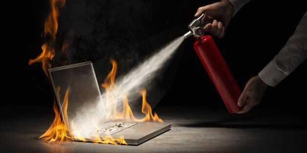 Businessman using fire extinguisher on laptop computer that is in