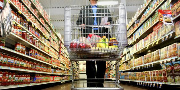 A man pushes his cart down a grocery aisle while shopping for