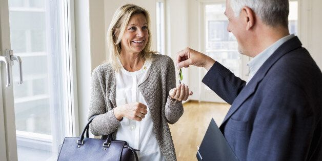 Happy male real estate agent giving keys to woman in new