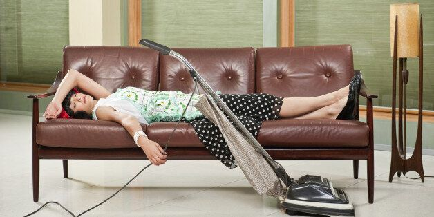 1950's housewife  with apron, napping on mid-sentury modern couch with Retro Hoover vacume cleaner