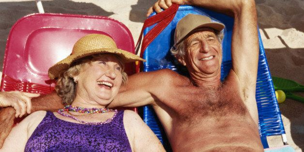 Senior couple lying on sun beds on beach, smiling