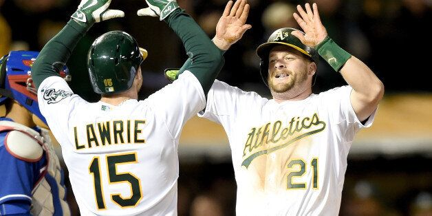 OAKLAND, CA - APRIL 06: Stephen Vogt #21 of the Oakland Athletics is congratulated by Brett Lawrie #15...