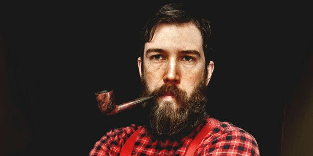 A man dressed as a lumberjack with a plaid shirt and suspenders has a big beard and a pipe in his