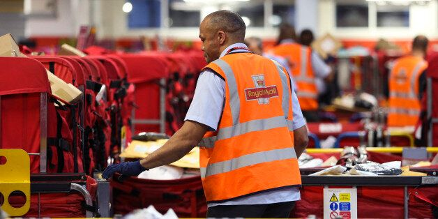 A Royal Mail Plc employee sorts parcels into red delivery destination trolleys at the company's Mount...