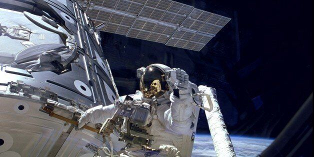 Astronaut James H. Newman waves during a spacewalk preparing for release of the first combined elements...