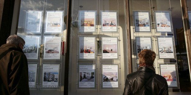 People looking art property signs displayed in the window of Marsh & Parsons estate agents in Notting...