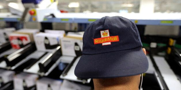 A logo sits on the cap of a Royal Mail Plc employee as he collects pre-sorted letters for delivery from...
